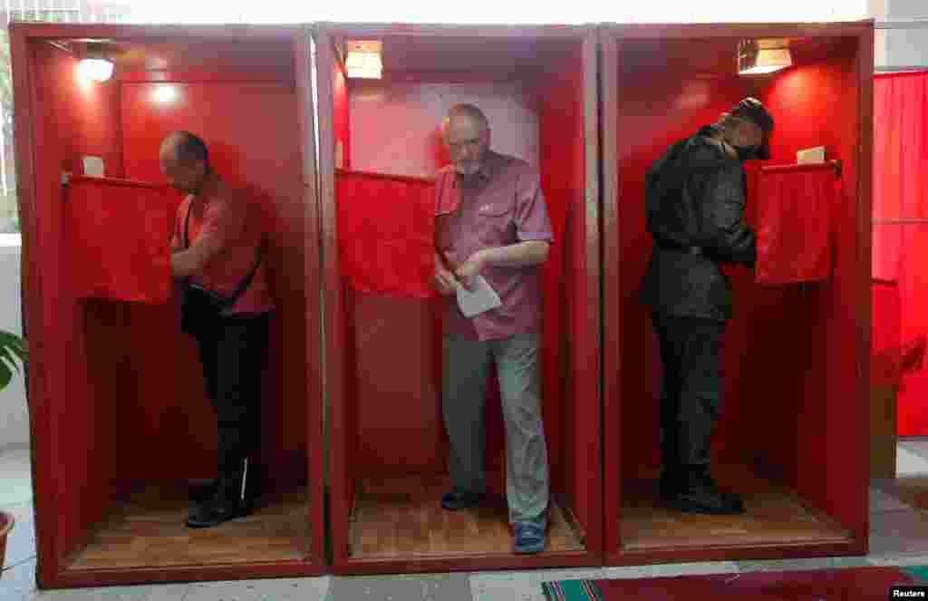 Люди голосують на виборчій дільниці у Мінську. Кабінка не зачинена з усіх сторін