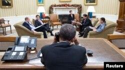 در این تصویر باراک اوباما (پشت به دوربین) در کاخ سفید واشینگتن در حال انجام گفتوگوی تلفنی با رائول کاسترو دیده میشود