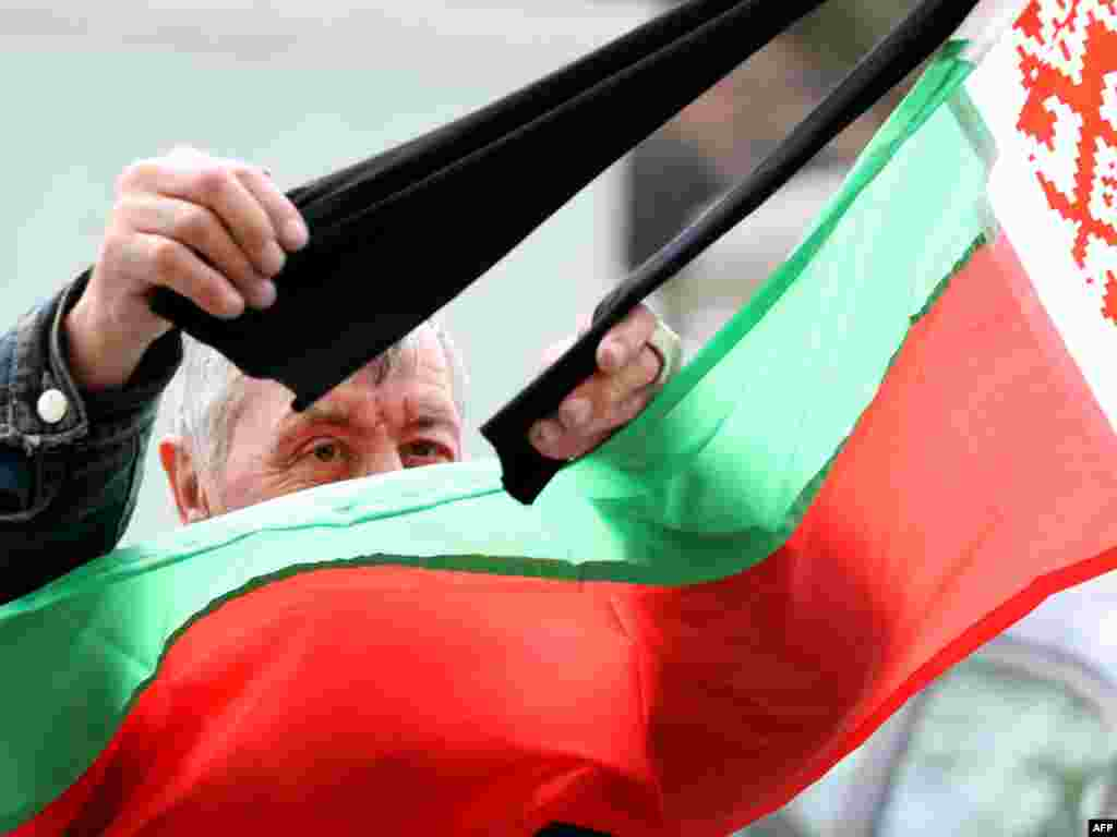 A man straightens mourning ribbons on the Belarusian flag in Minsk on April 13, two days after the blast that killed at least 13 people. Photo by Alexey Gromov for AFP