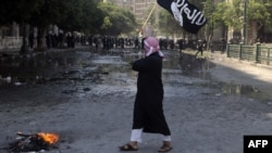 An Egyptian protester holds an Al-Qaeda affiliated flag near the U.S. Embassy in Cairo on September 14.