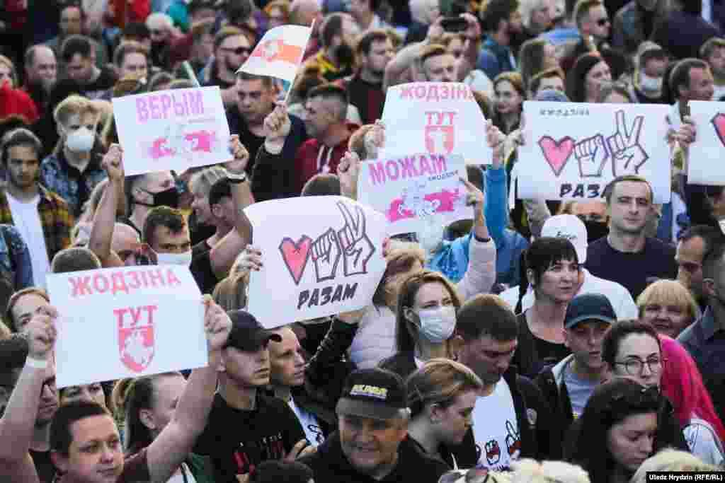 """Oamenii țineau pancarte cu sloganurile: """"Împreună"""", """"Putem"""" și """"Credem""""."""