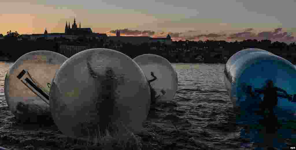 Tourists play in Zorb balls on the Vltava River during a hot summer evening in central Prague. (epa/Filip Singer)