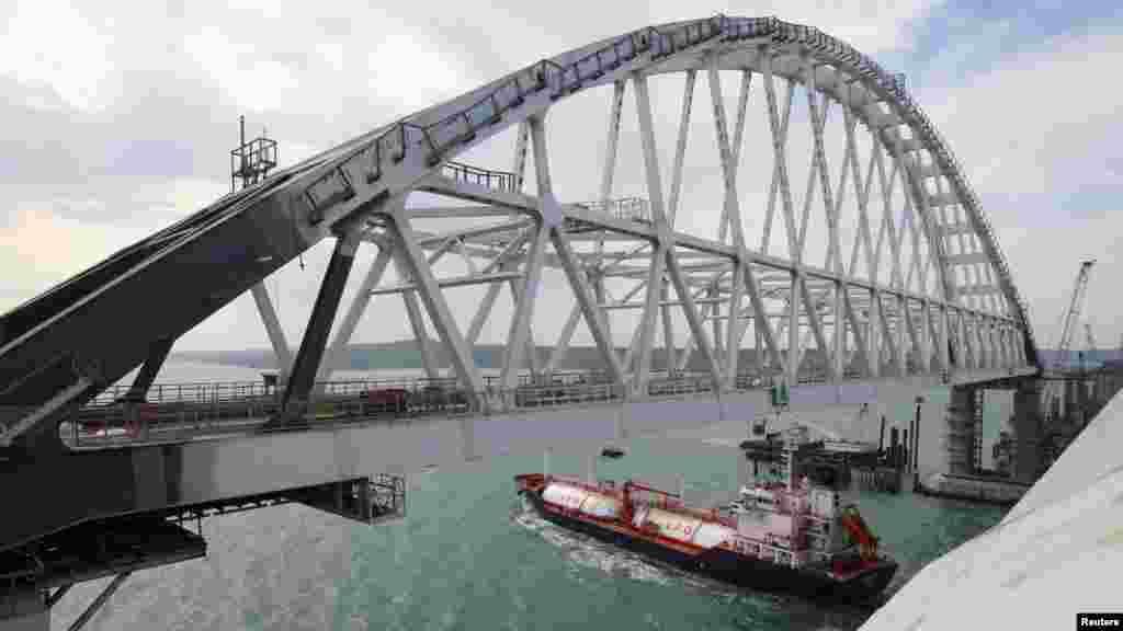 Корабель проходить під аркою. В українських портах Бердянська і Маріуполя заявили, що Керченський міст зупинив розвиток бізнесу морських перевезень – відрізав їх від ринків збуту, ускладнивши умови проходження великих вантажних суден океанічного класу