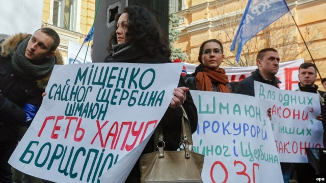 Ukrainian activists hold placards during their rally in front of the presidential office in Kyiv, demanding the resignation of Prosecutor-General Viktor Shokin.