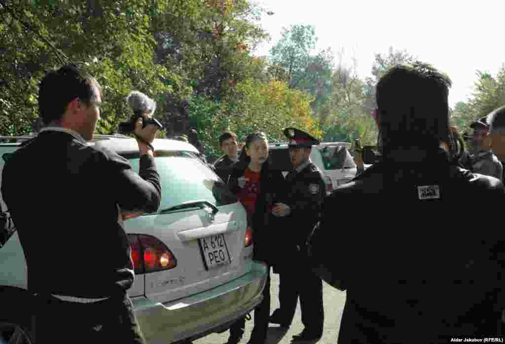 Полицейские уводят зачинщицу срыва пресс-конференции оппозиционеров Гульбахрам Жунис - Полицейские уводят Гульбахрам Жунис, зачинщицу срыва пресс-конференции оппозиционеров. Алматы, 27 октября 2010 года.
