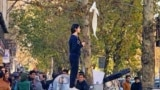 """For more than a year now, the """"Girls of Revolution Street"""" (and a few men) have conducted sporadic one-person protests against the hijab by removing their head scarves and waving them in crowded public spaces in the capital."""