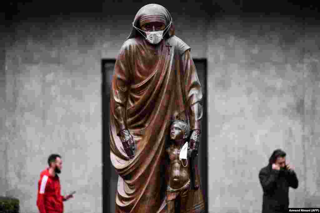 A statue of Saint Teresa in Kosovo's capital, Pristina, is covered with a surgical mask on December 19. (AFP/Armend Nimani)