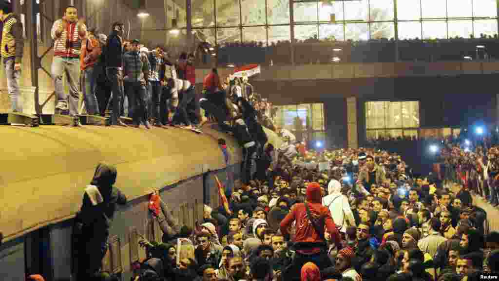People gather around a train as they wait in Cairo for the arrival of those wounded during deadly rioting at a soccer stadium in Port Said. (REUTERS)