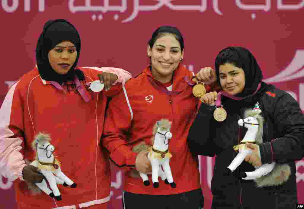 The United Arab Emirates' Yasmin Abbas (right) celebrates her bronze medal in weightlifting in Qatar in December. The UAE has been cleared to send a team to the London Olympics, the first team to compete in Islamic dress.