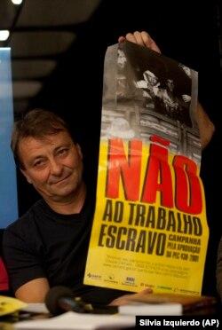 باتیستی با پوستر «نه به بردهداری» در دست، در زمان رونمایی از کتابی درباره خاطرات زندان در برزیل در سال ۲۰۱۲