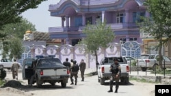 Security officials stand guard in front of the house of Arsala Rahmani, senior peace negotiator, in Kabul, after his murder.