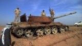 جنود عراقيون فوق دبابة متضررة كانت لداعش، تكريت 24 شباط 2015