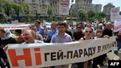 "People shout slogans as they hold placards and a banner reading ""No gay parade!"" during an antigay rally in Kyiv on May 14."