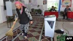 Женщина подметает ковер на избирательном участке в селе Таш-Мойнок, который находится в 20 киломтерах от Бишкека, 2 октября 2015 года. Иллюстративное фото.