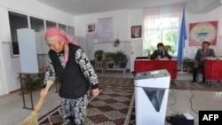 Женщина подметает ковер на избирательном участке в селе Таш-Мойнок, который находится в 20 километрах от Бишкека, 2 октября 2015 года. Иллюстративное фото.