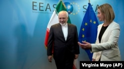 European Union High Representative Federica Mogherini, right, greets Iran's Foreign Minister Mohammad Javad Zarif prior to a meeting in Brussels on Monday, March 16, 2015.