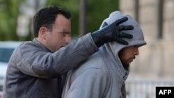 Підозрюваного в нападі (п) веде працівник спецбригади поліції, Париж, 29 травня 2013 року