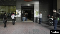 Люди стоят у здания биржи труда в Афинах.