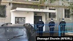 Коронавирусқа байланысты карантинге жабылған тұрғын үйдің алдында тұрған полиция қызметкерлері. Ақтөбе, 30 сәуір 2020 жыл.