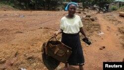 Жена држи јакна на војник кој наводно загинал во лизгањето на земјиште во Сиера Леоне.