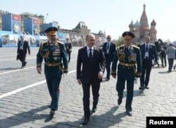 Министр обороны России Сергей Шойгу, президент России Владимир Путин и командующий парадом генерал-полковник Олег Салюков идут по Красной площади после завершения парада. Москва, 9 мая 2015 года.