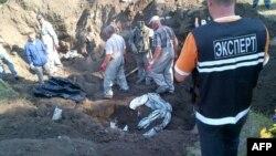Эксперты раскапывают братскую могилу в украинском городе Славянск, в которой были захоронены тела четырех неизвестных человек. 24 июля 2014 года.