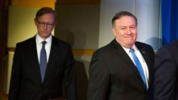 Secretary of State Mike Pompeo, right, followed by Brian Hook, special representative for Iran, walk to a podium to announce the creation of the Iran Action Group at the State Department, in Washington, Thursday, Aug. 16, 2018.