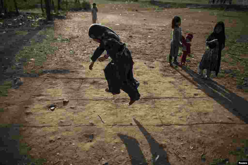 A girl jumps as she plays hopscotch on the outskirts of Islamabad, Pakistan. (Reuters/​Zohra Bensemra)