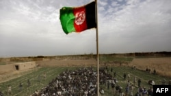 The Afghan national flag is hoisted during an official flag-raising ceremony on February 25 in Marjah, a former insurgent stronghold.
