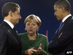 French President Nicolas Sarkozy (left), his U.S. counterpart, Barack Obama, and German Chancellor Angela Merkel talk in Cannes on November 3.