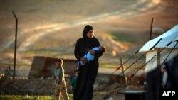 Сириядагы качкындар лагерлеринин биринде баласын көтөргөн аял. 26-март, 2017-жыл. Иллюстрациялык сүрөт.