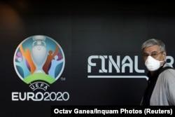 Турист проходит мимо логотипа чемпионата Европы по футболу 2020 года. Бухарест, Румыния. 16 марта 2020 года.