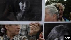 Politički aktivisti drže portret ubijene aktivistkinje za ljudska prava Natalije Estemirove