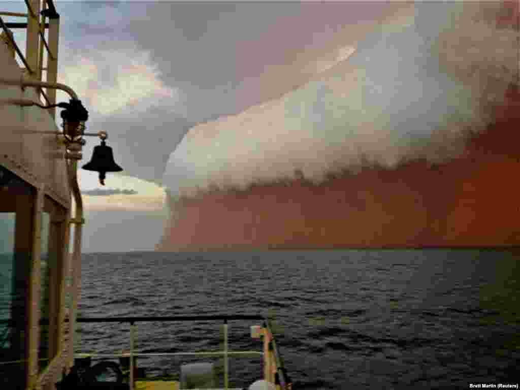 A dramatic cloud formation tinged with red dust travels across the Indian Ocean near Onslow on Australia's west coast on January 9.