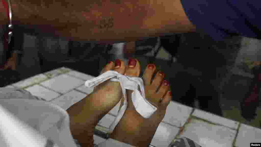 The feet of a slain antipolio worker are tied by rescue workers after her body was brought to Jinnah Hospital morgue in Karachi on December 18. (Reuters/Akhtar Soomro)