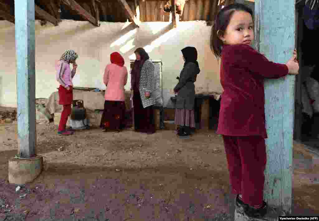 KAZAKHSTAN -- A young girl looks at the camera during a feast held for the neighbours and relatives of Malik Yasyrov - a Dungan man, Kazakh language teacher who died from a gunshot wound in the Masanchi attacks - who helped bury him in the settlement of S