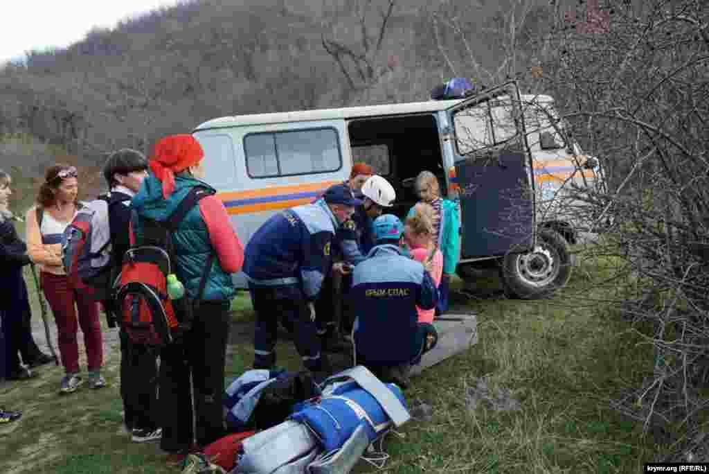 Спасатели накладывают шину потерпевшей, которая упала с четырехметровой высоты близ водопада Гейзер