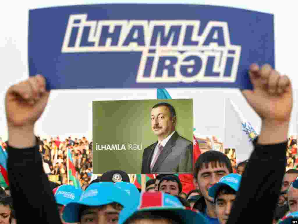 Caption: epa01519130 Azeri people hold placards and posters reading Ilham go forward in front of pre-electoral posters showing candidate and Azerbaijan present President Ilham Aliyev during a rally supporting his candidacy at the upcoming president elections in Sumgait, some 30km from Baku, Azerbaidjan, 13 October 2008.