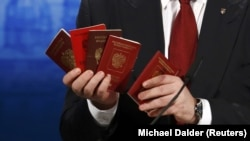 Паспорти і військові квитки громадян Росії, які воювали в Україні, в руках Петра Порошенка на Мюнхенській конференції, 7 лютого 2015 року