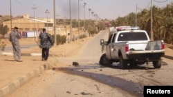 Iraqi police inspect the site of militant attack in the town of Haditha on March 5.
