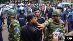 Bangladeshi police and military gather in an intersection near an upscale restaurant after a bloody siege ended in Dhaka on July 2.