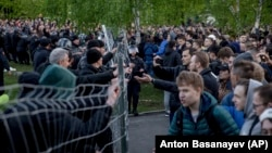 Demonstrators (right) stand outside a fence blocked by police as they protest plans to construct a church in a park in Yekaterinburg on May 14.