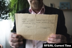 Valery Borshchev shows the paper he was given in 1995, at his home in Moscow on May 29, 2020.