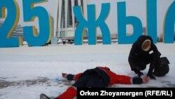 Художник Асхат Ахмедьяров (на земле) изображает расстрелянных пять лет назад участников демонстрации в городе Жанаозене, гражданская активистка Сауле Батал рисует на земле краской контур его тела. Астана, 21 декабря 2016 года.