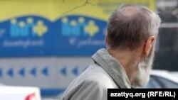 Пожилой мужчина смотрит на рекламу накопительного пенсионного фонда. Алматы, 29 марта 2012 года.