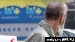 Жинақтаушы зейнетақы қорының баннеріне қарап тұрған зейнеткер. Алматы, 29 наурыз 2012 жыл. (Көрнекі сурет)