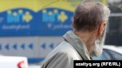 Жинақтаушы зейнетақы қорының көшедегі баннеріне қарап тұрған адам. Алматы, 29 наурыз 2012 жыл.