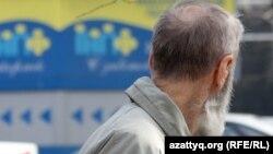 Жинақтаушы зейнетақы қорының жарнамасына қарап тұрған қарт. Алматы, 29 наурыз 2012 жыл.