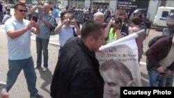 Майор полиции Окопный уносит свой портрет, вырванный из рук демонстрантов. Видео - гражданский журналист TVKeep