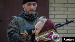 A woman walks past a Ukrainian serviceman as he stands guard in Volnovakha, Donetsk region.